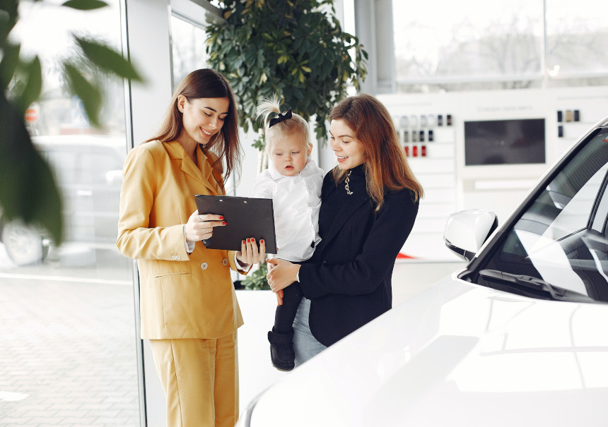 Woman with baby shopping for cars